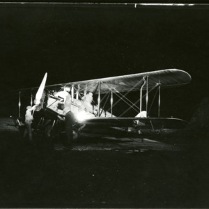 Airplane and men on field, 1930