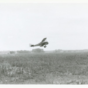 Air Mail plane flying over field,. 1923