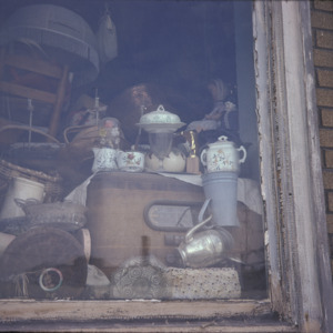 Antiques in the Window at Dicker's Furniture, 301 S Dubuque St, 1975